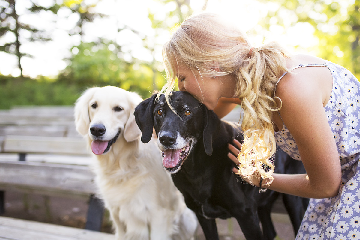 blond girl kissing black lab dog